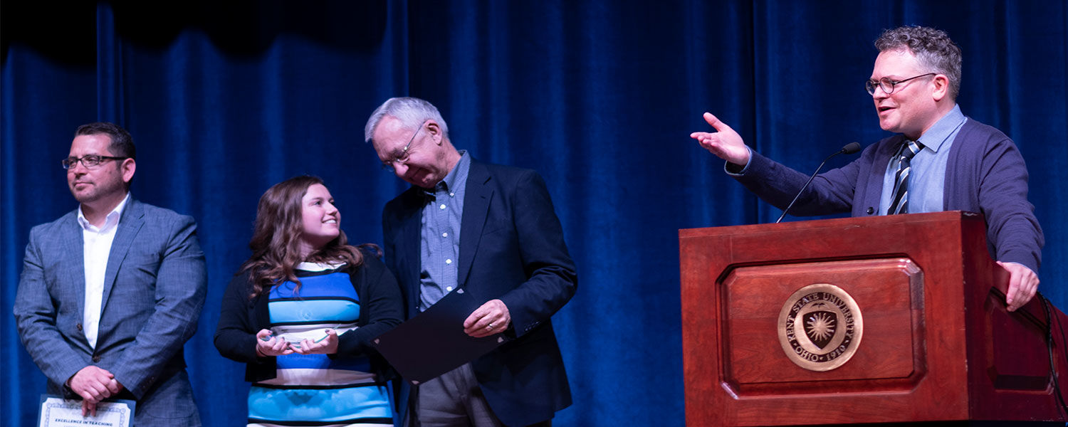 Assistant Professor Aaron Bacue congratulates the participants in the Hyde Park Forum as the 2018 champion, Alexa Kwiatkowski, whispers to her instructor David Zachrich.