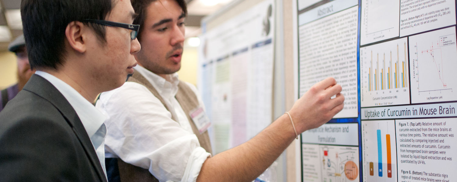 A student describes his research to a faculty judge during the annual Honors Week Poster Session.