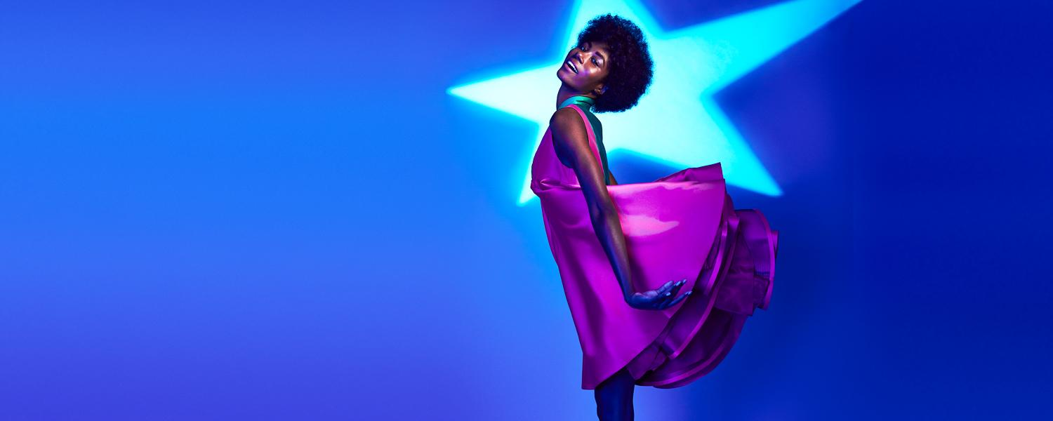A hero photo of a model in a pink dress on a blue background