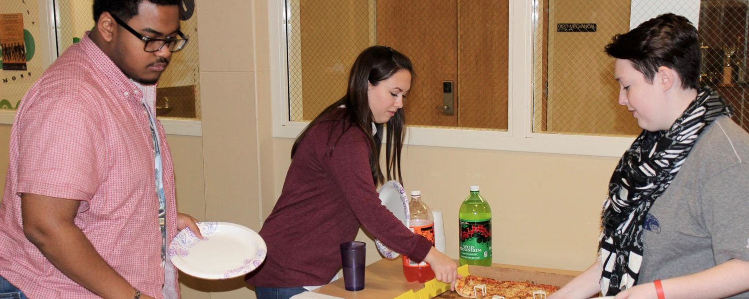 Students enjoy pizza at a meeting on campus