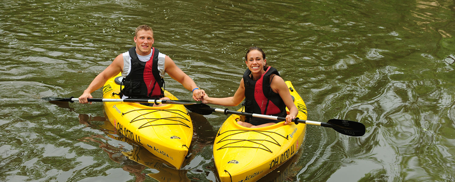Two students posing for photo in canoes