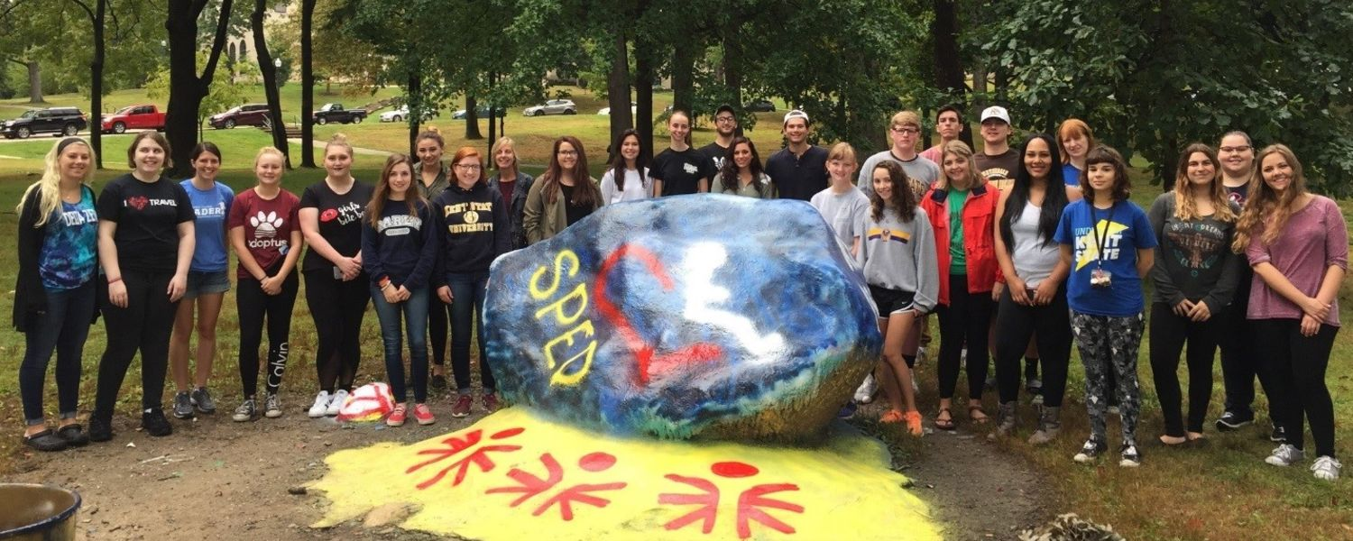 Special education students painting the rock
