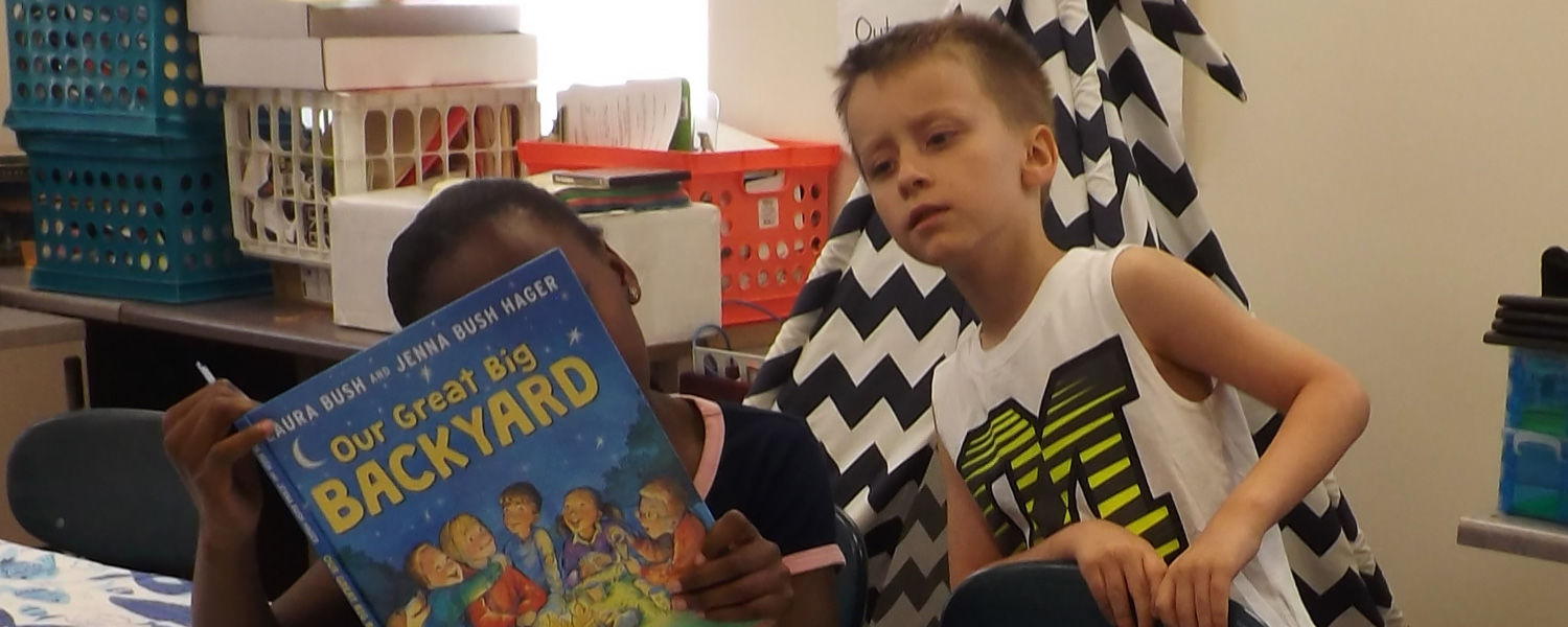 Children looking at a book at Camp Read-a-Lot
