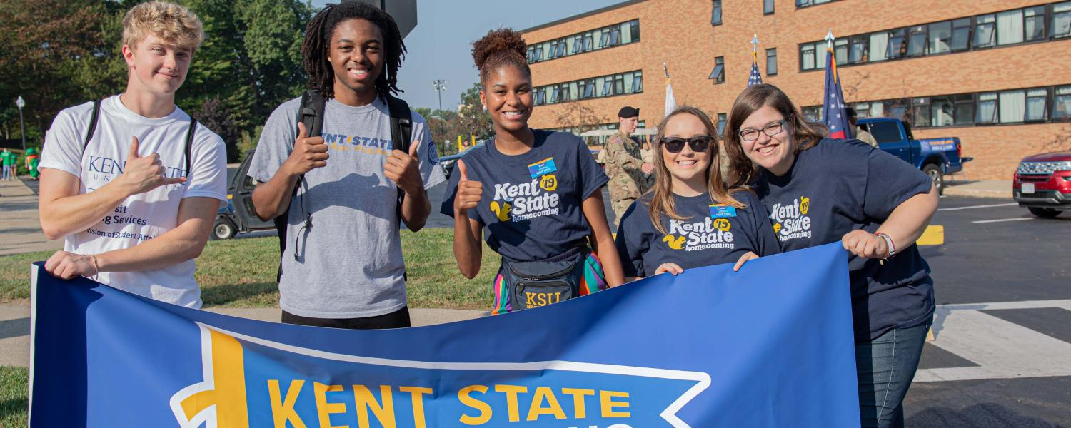 Kent State students hold a Kent State Homecoming banner for the Sept. 21, 2019 Homecoming parade.