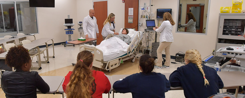 Ashtabula nursing students work on the patient simulator during class