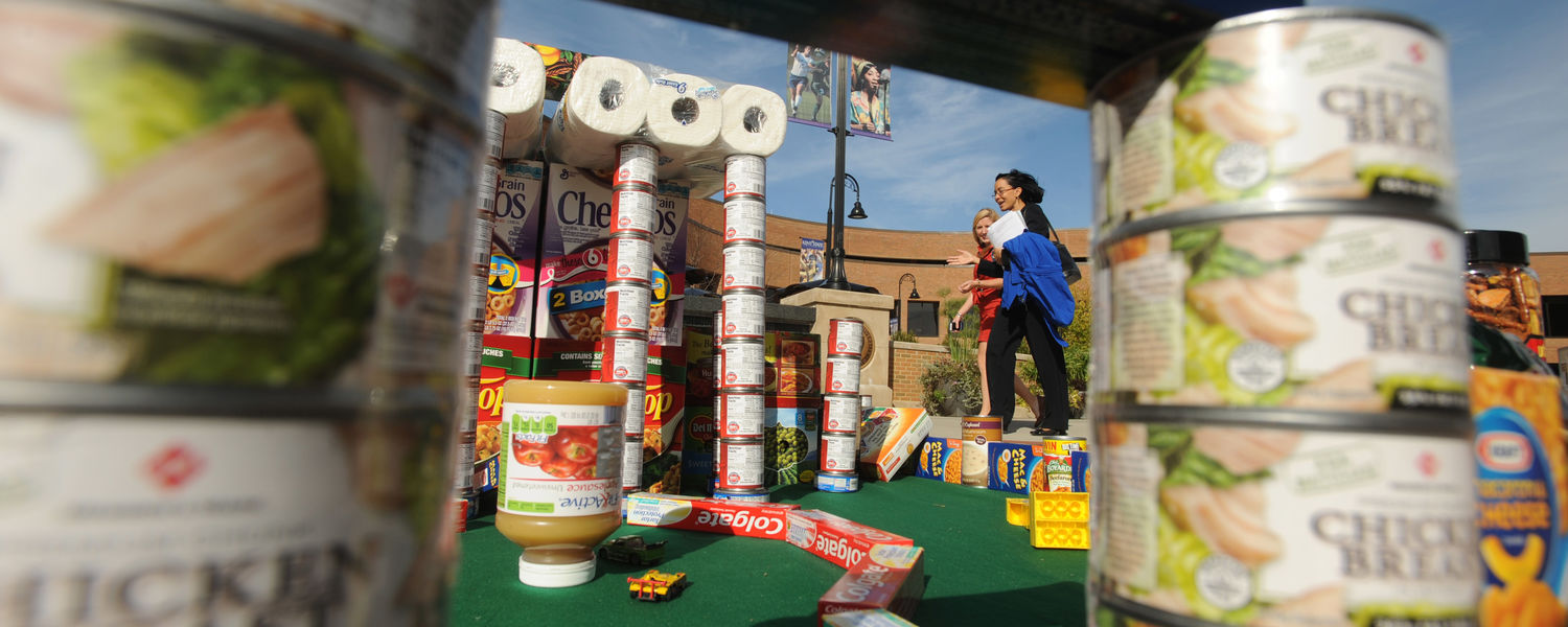 Students walk by a sculpture made from canned food and other donated items that was built in the Risman Plaza. The project was a contest for the United Way food drive.