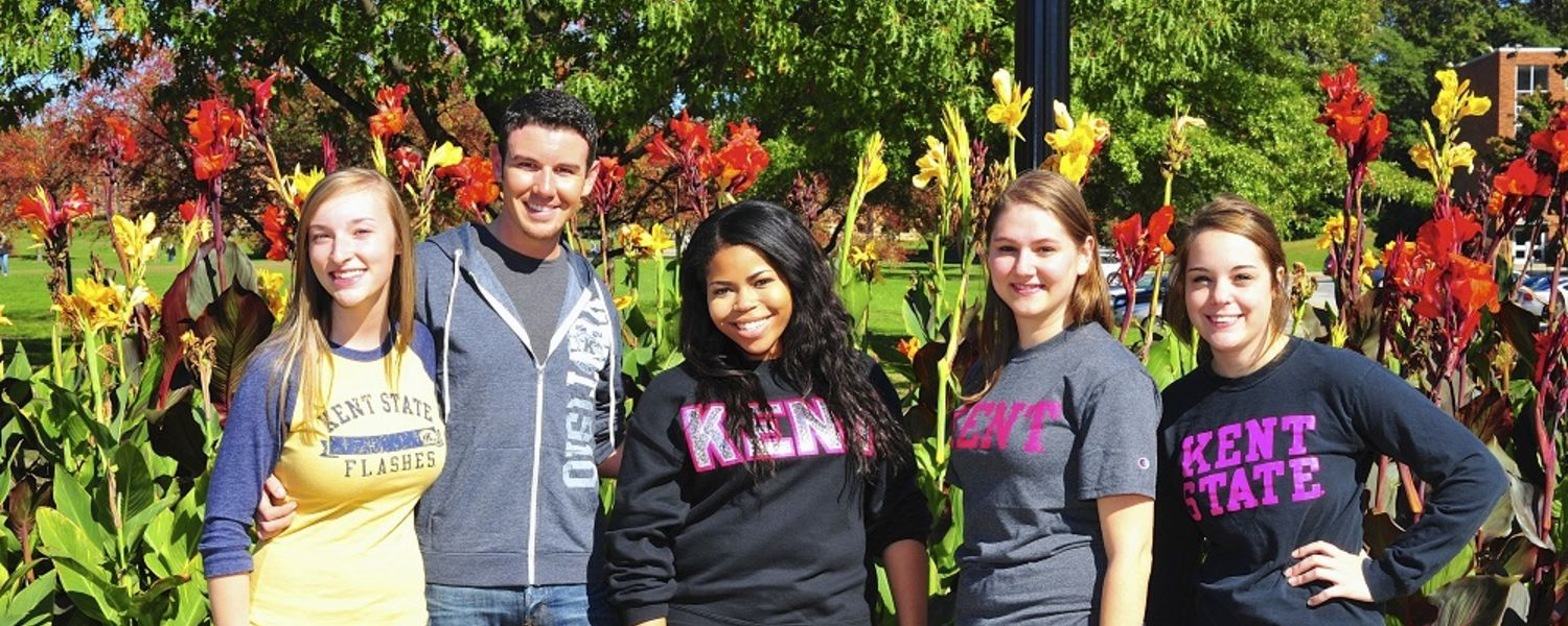 A group of students take a photo in the flower garden on campus.