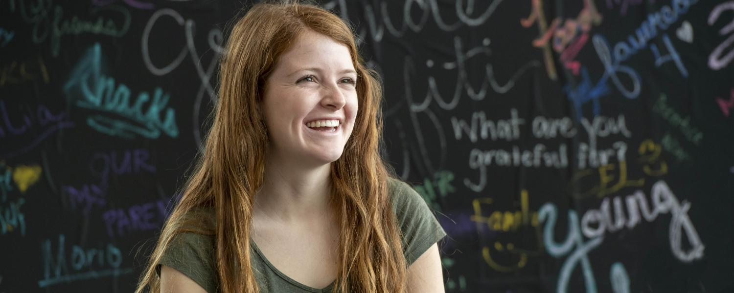 A student sits and smiles in front of a gratitude board on the Kent Campus.