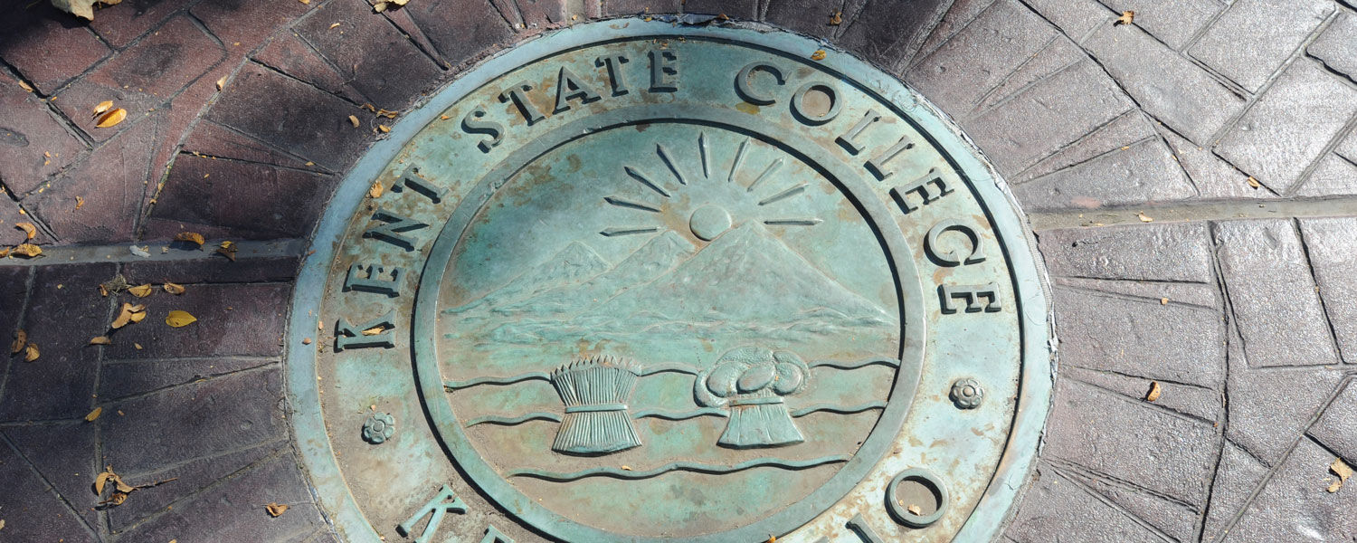 The seal of Kent State College, as it was known at the time, is embedded into the brick sidewalk in front of the Prentice gate on front campus.