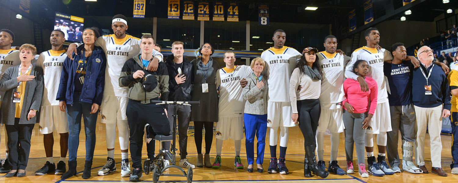 President Beverly Warren singing the National Anthem with the basketball team
