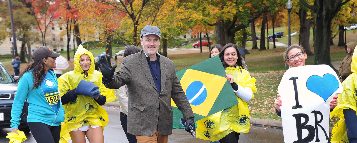 Provost Diacon and students walking in Homecoming parade.