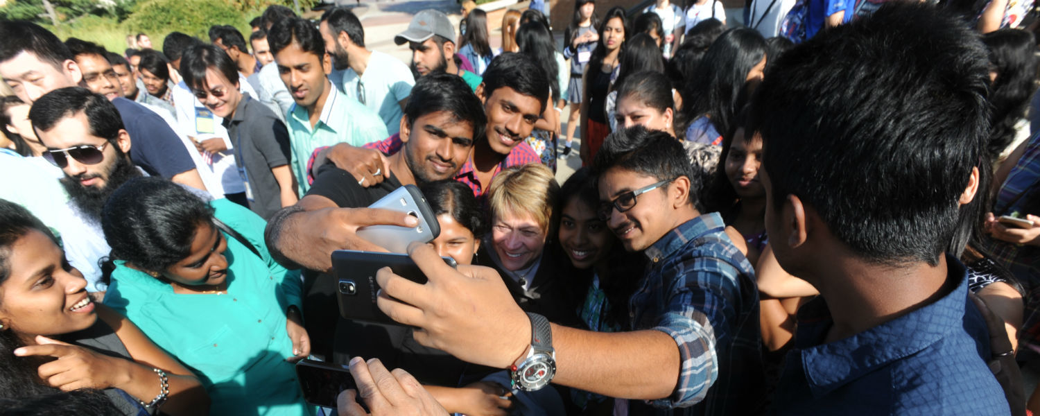 Students taking a selfie with President Warren