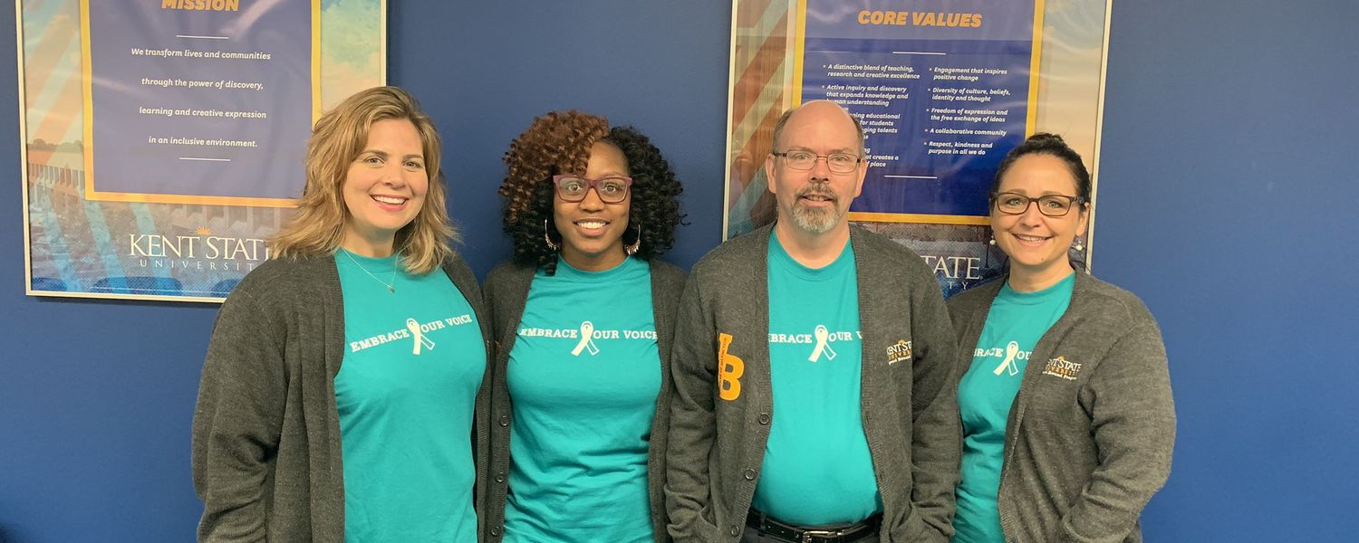 group photo of 4 individuals wearing Sexual Assault Awareness Month shirts