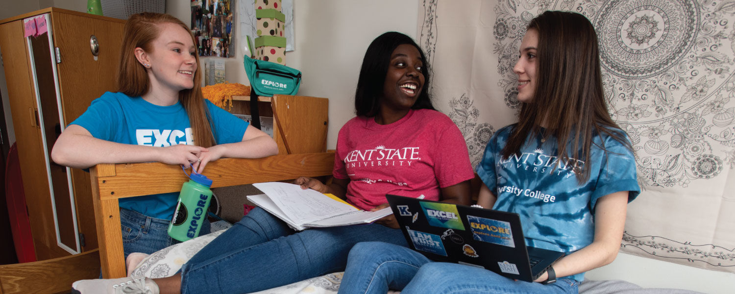 Three students sitting in dorm room.