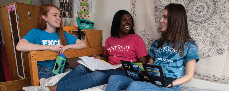 Three students sitting in dorm room.