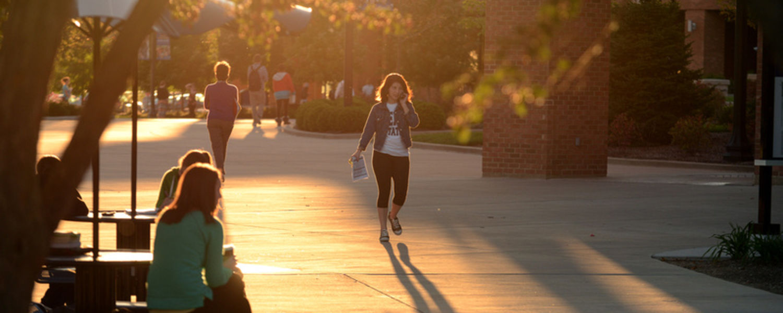 A student walks through the Risman Plaza on a warm fall evening.