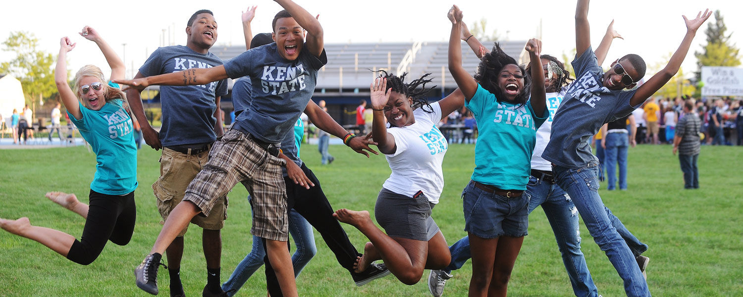Banner image of students jumping in a field