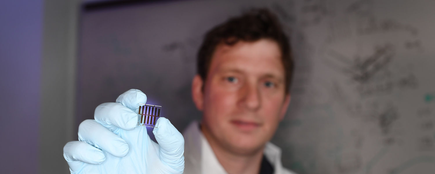 Bjorn Lussem holds on of the many organic transistors he studies in his lab