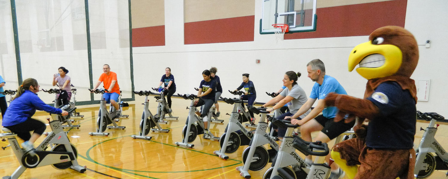 Kent State University faculty and staff, along with mascot Flash, enjoy a spin class at the Fac/Staff Rec & Play Day.