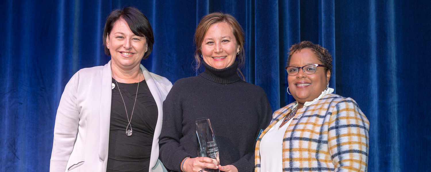 On behalf of the Kent State University Fashion School's NYC Studio, Ann Walter (center), the studio's director, accepts the 2020 Beverly J. Warren Unity Award for Diversity from Dana Lawless-Andric (left) and Sonya Williams (right).