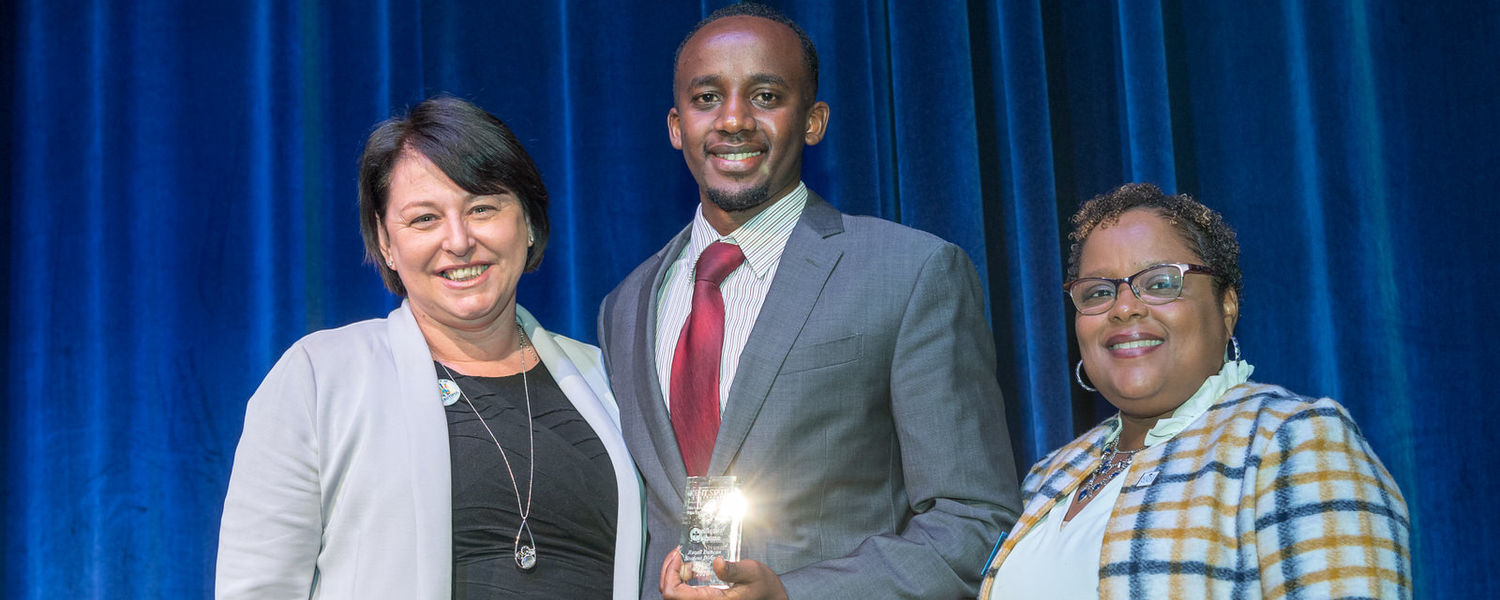 Kent State University Ph.D. candidate Pacifique Niyonzima (center) receives the 2020 Rozell Duncan Student Diversity Award from Dana Lawless-Andric (left) and Sonya Williams (right), both from the Division of Diversity, Equity and Inclusion.