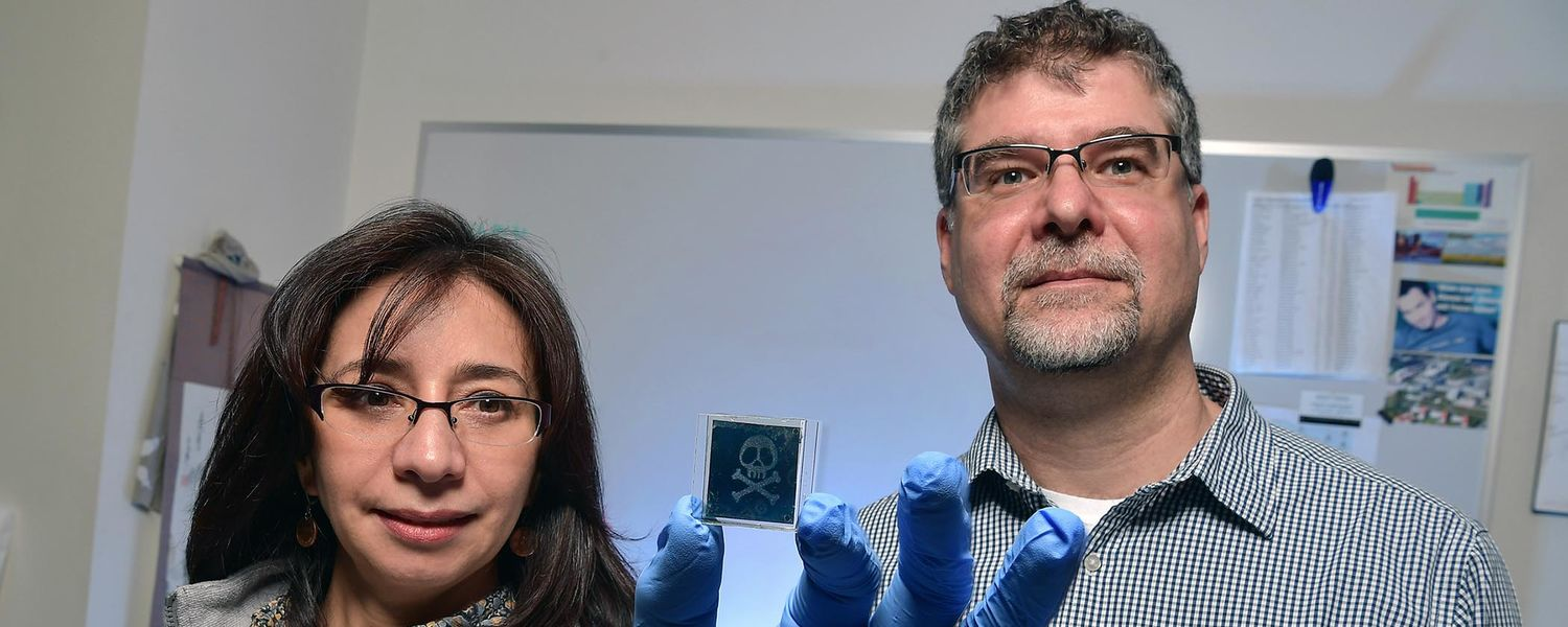 Kent State University researchers Elda and Torsten Hegmann pose with one of the sensors they created that detects toxic gases. The sensors can be made any shape or size and require no power to function.