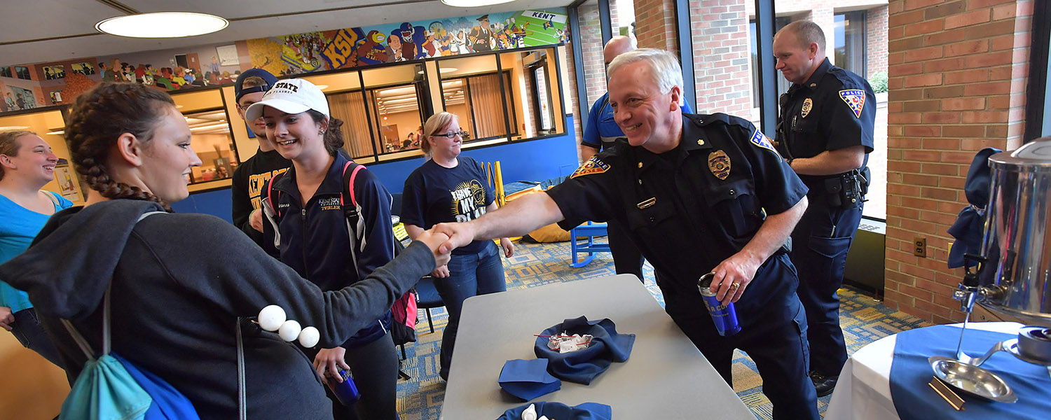 Bill Buckbee (right), assistant director of public safety and assistant chief of police at Kent State University, shakes hands with a student during a Coffee With a Cop event.