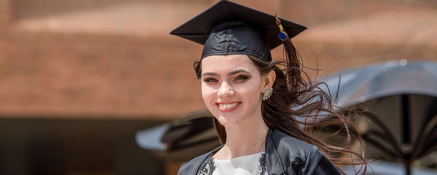 A graduating Kent State University student smiles in her cap and gown at Risman Plaza in spring 2020.