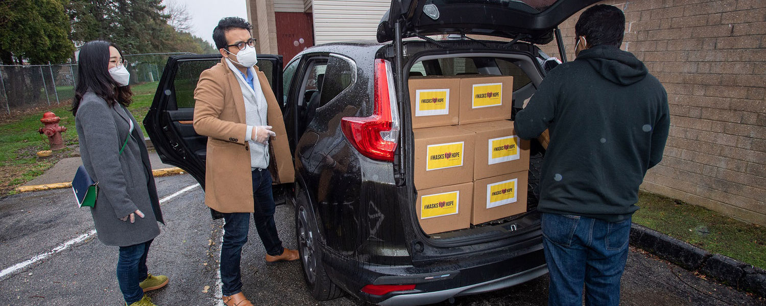 Kent State University students, including Yuqiao Xu (far left) and Irvin Cardenas (center), load medical supplies to be donated to Cleveland Clinic into a vehicle.