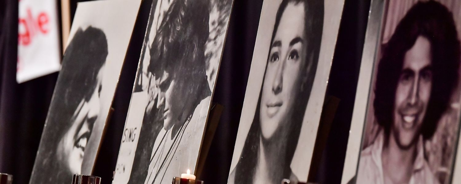 Portraits of the four students killed on May 4, 1970, sit on chairs on stage in the Kent Student Center Ballroom during the 47th Commemoration of May 4.