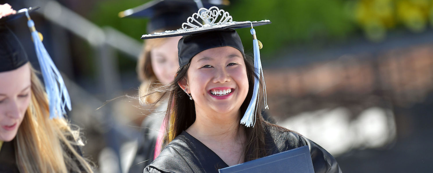 A new Kent State University graduate smiles after receiving her diploma.