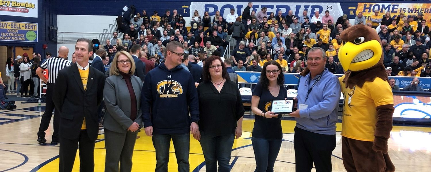 Megan Conrad (fifth from left) is recognized at a Kent State basketball game. She is joined by her family along with representatives from Kent State's administration, College of Business Administration, PNC and Flash, the mascot.
