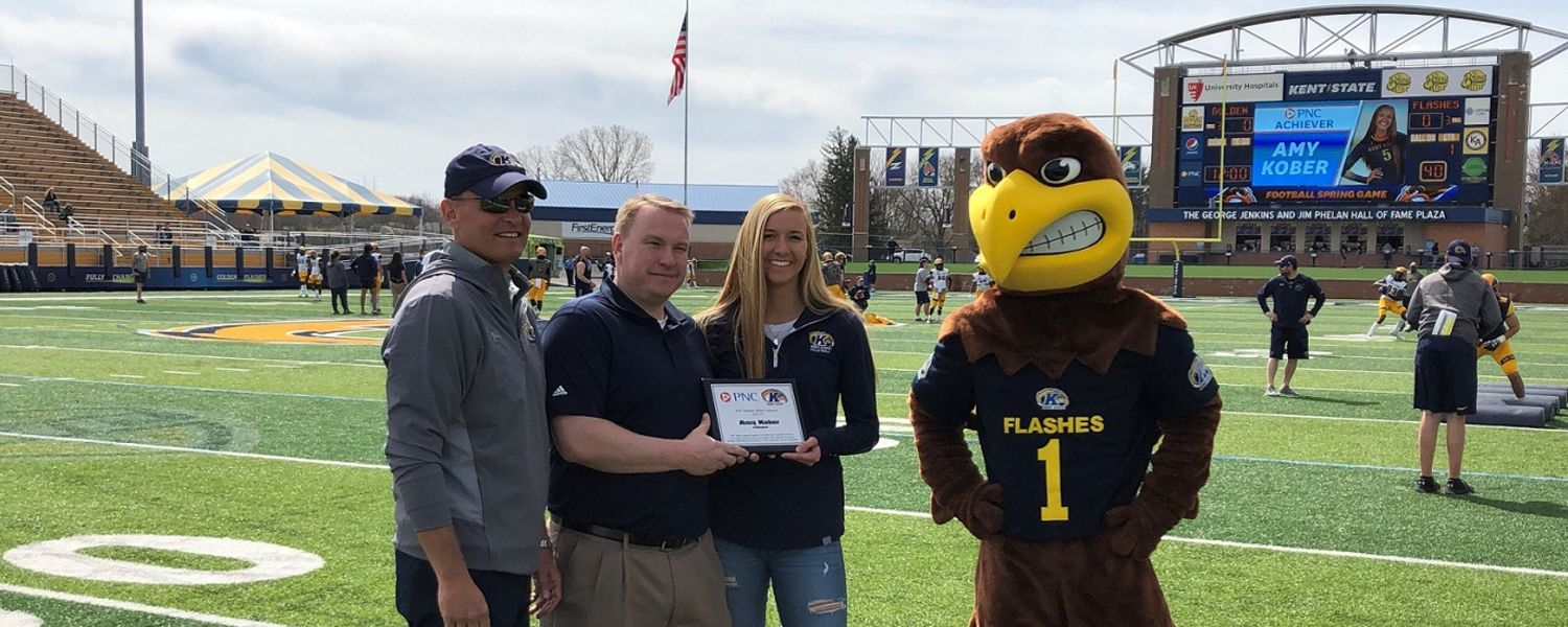 Amy Kober (third from left) is recognized at the Kent State football spring game. She is joined by Kent State Director of Athletics Joel Nielsen (far left), PNC Senior Vice President of Corporate Banking Don Pavlik and Flash, the mascot.