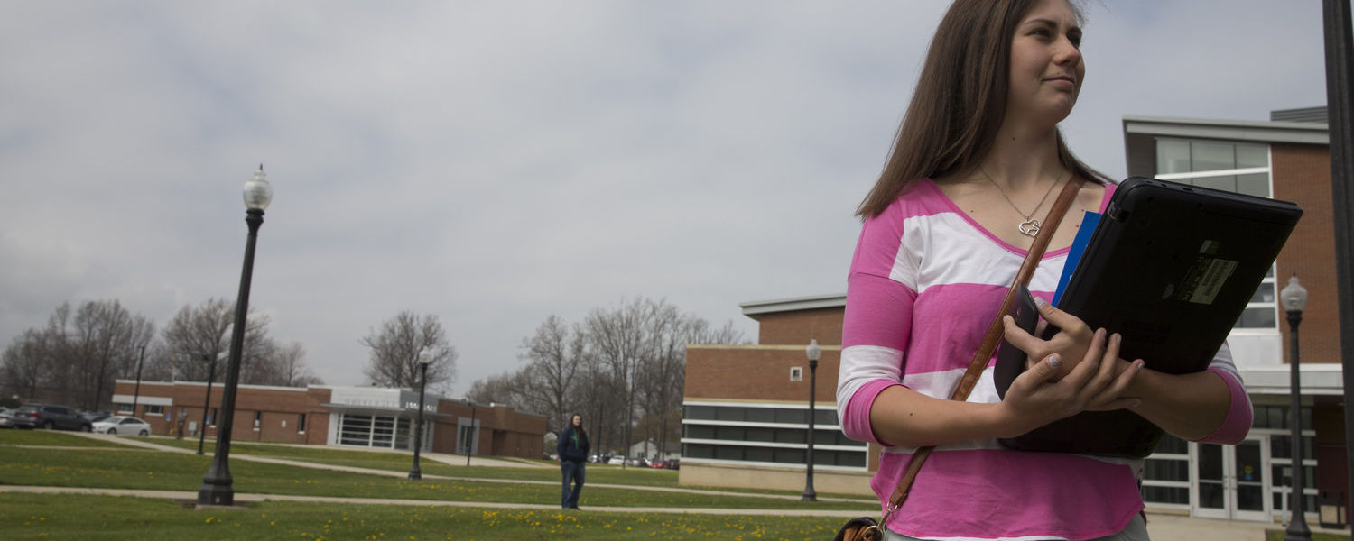 Student with campus in the background.