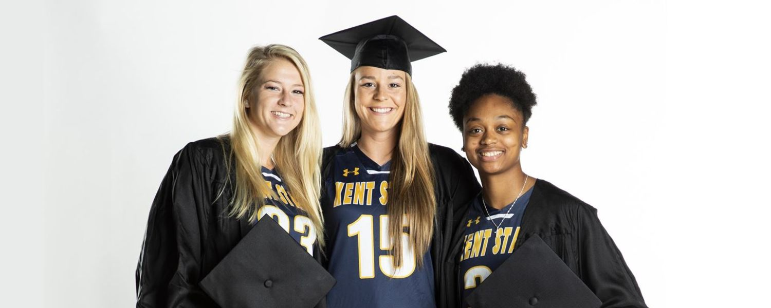 Kent State women's basketball players and graduating seniors Ali Poole, Sydney Brinlee and Megan Carter smile with their caps and gowns. (Photo credit: Scott Galvin)