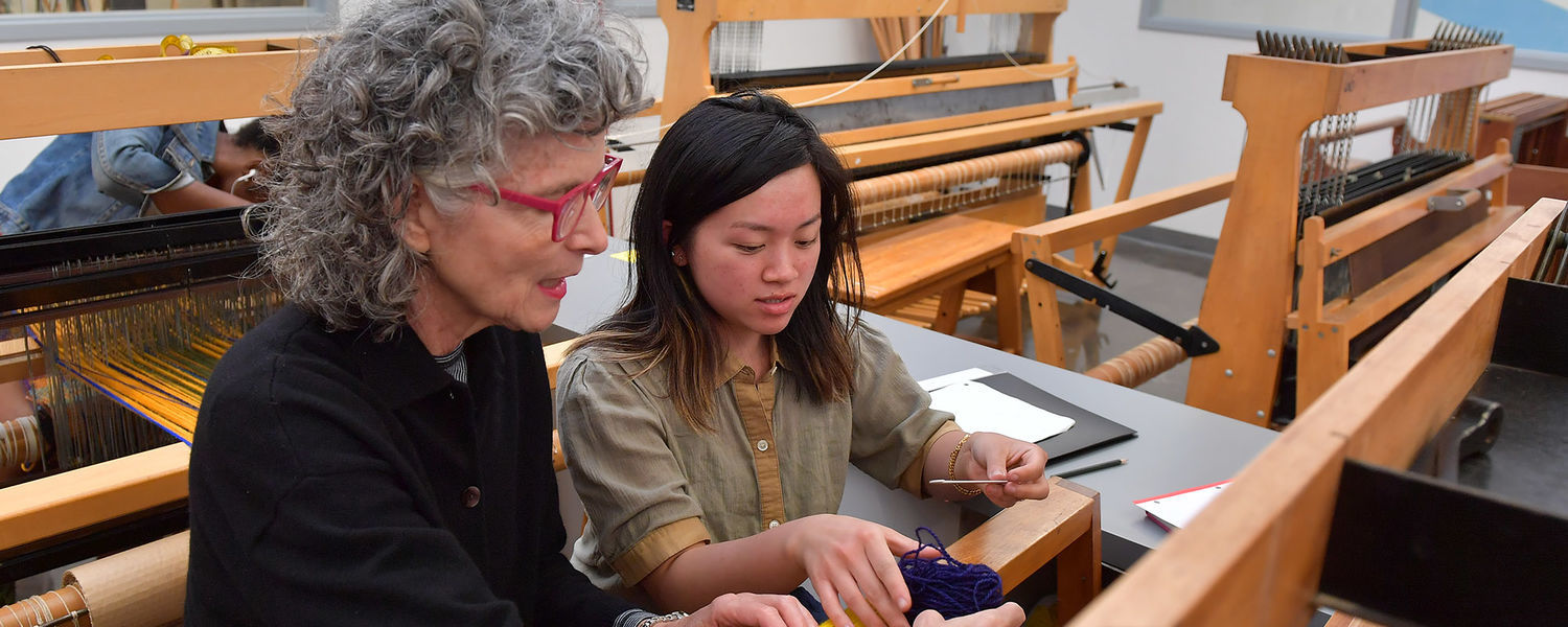 Janice Lessman-Moss (left), professor of textile arts at Kent State University, works with a student on a weaving loom in the Center for the Visual Arts.
