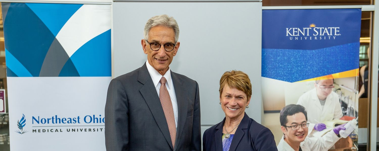 Northeast Ohio Medical University President Jay Gershen and Kent State University President Beverly J. Warren pose for a photo after signing a shared services agreement.