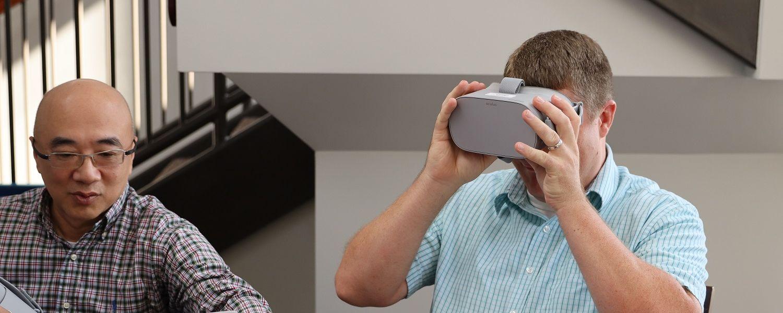 Cheng Chang Lu, Ph.D., works on his computer while Karl Kosko, Ph.D., wears virtual reality goggles.