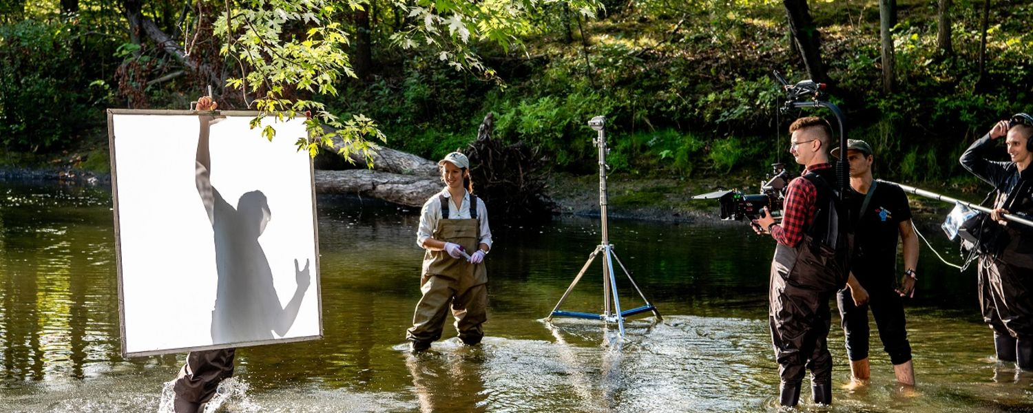 A Kent State University graduate biological sciences – ecology student stands in the river with a video crew to record a scene for the new Kent State TV commercial.