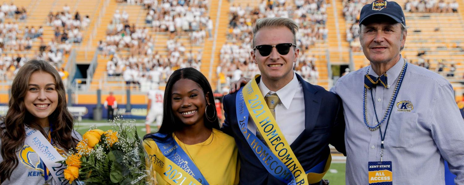 Jatia Caples (second from left) and Andrew Pitko (third from left) are announced as the 2021 Homecoming Royalty during halftime of Kent State's Homecoming football game at Dix Stadium. They are joined by a member of 2020 Homecoming Royalty.