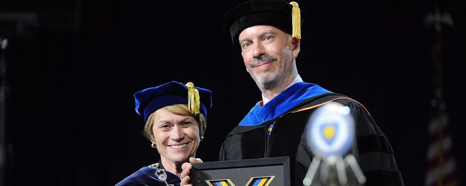 Kent State University President Beverly Warren presents Earl K. Miller, Ph.D., with a Kent State Alumni Association Professional Achievement Award during the Spring 2016 Commencement ceremony at the Memorial Athletic and Convocation Center.