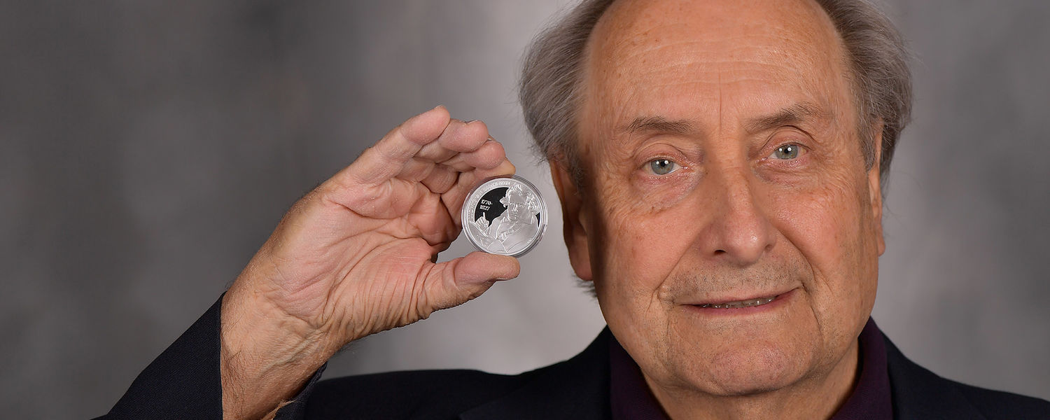 Theodore Albrecht, Ph.D., professor of musicology in Kent State University's Hugh A. Glauser School of Music, holds the Beethoven Medal he was awarded in recognition of his musicological contributions to the study of composer Ludwig van Beethoven.