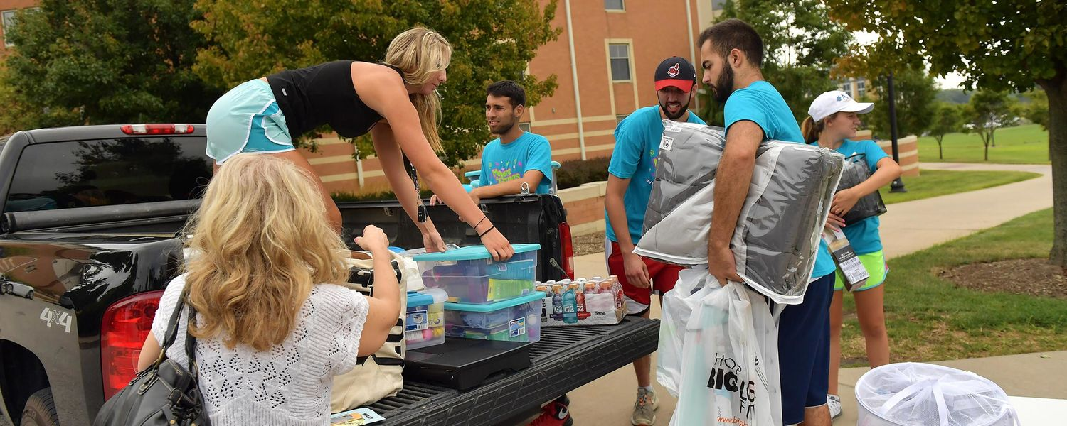 Kent State student volunteers help a new student unload her belongings from a pickup truck.