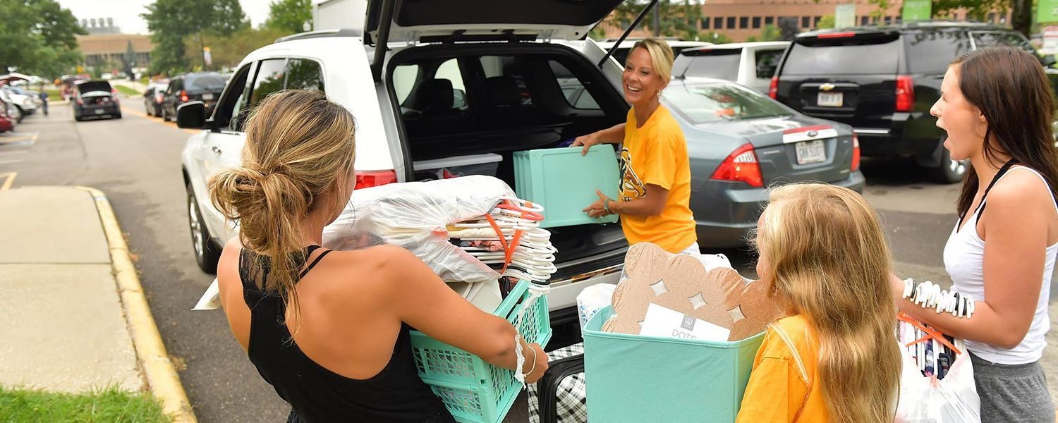 The mother of a new Kent State student unloads items from the back of their car. The family drove from Virginia to bring their daughter to Kent State.
