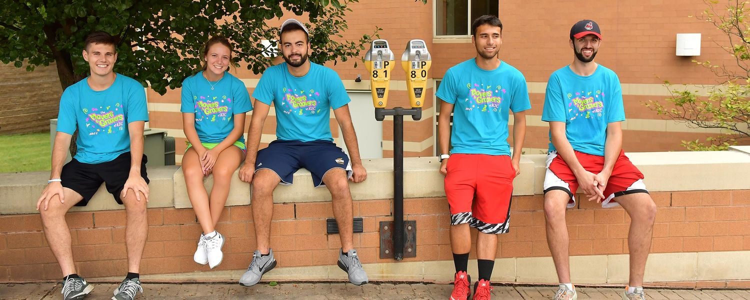 Kent State student volunteers take a break in the shade near Centennial Court A during freshman move-in day.