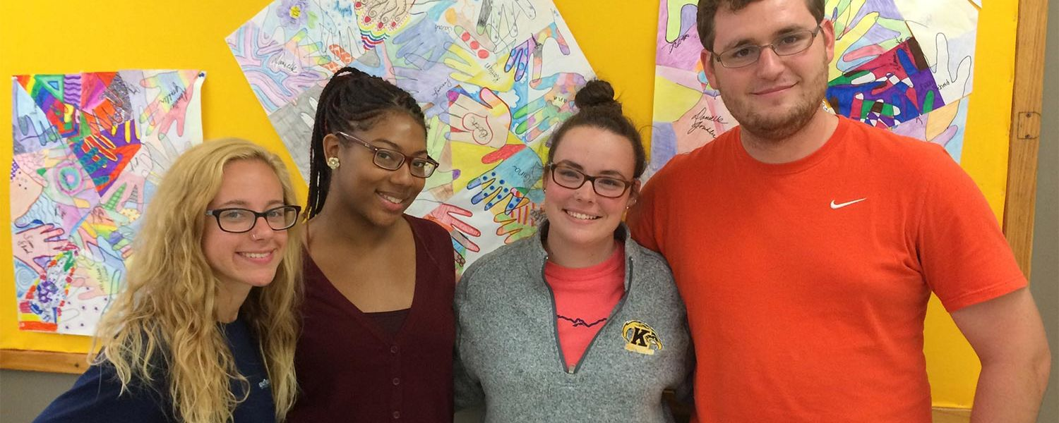 Kent State University students studying middle childhood education pose in front of their artwork in their Teaching and Learning class in White Hall.