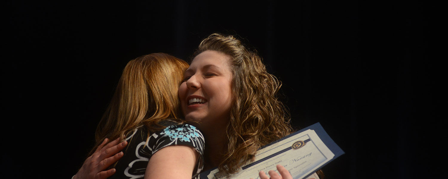 Cindy Wilk, MSN, RN, CNS, CCRN, CNE, coordinator of the Adult Gerontology Clinical Nurse Specialist concentration, left, hugs Erica Stahl after presenting her with a certificate and pin.