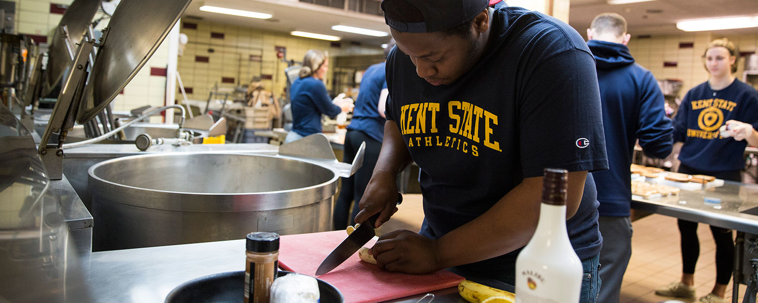 A Kent State student volunteers in the Campus Kitchen at Kent State to help prepare meals for those in need.