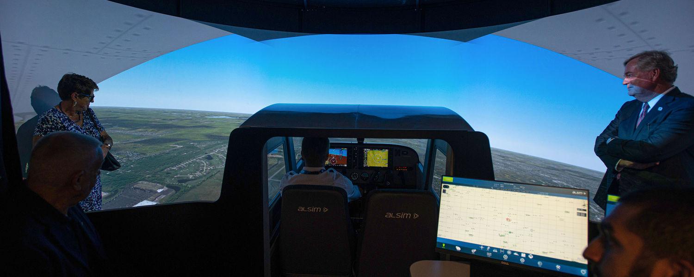 A group touring the FedEx Aeronautics Academic Center looks at one of the new flight simulators.