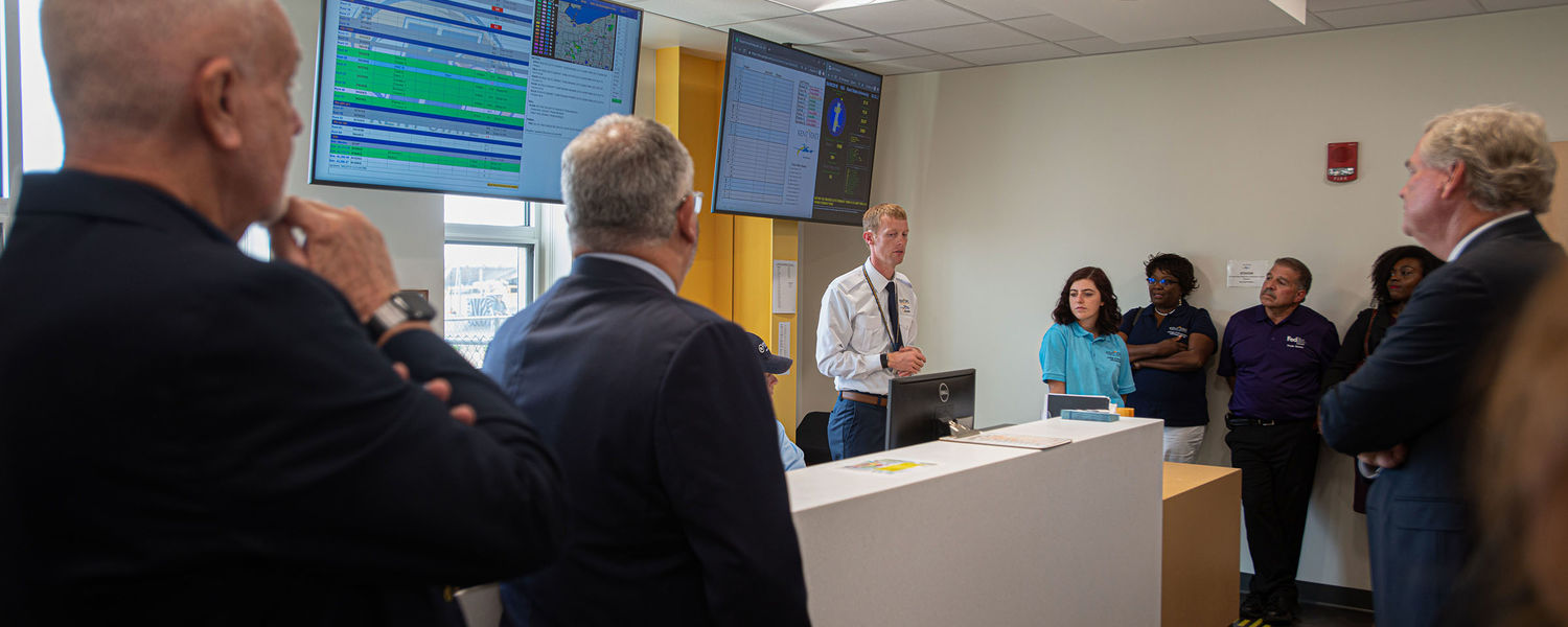 Brian Neff (center), chief flight instructor at the Kent State University Airport, gives a tour of the flight operations center at the new FedEx Aeronautics Academic Center.